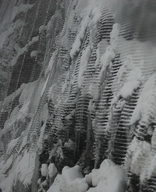 CHAIN LINK CURTAINS OVER THE CLIFFS IN AN ATTEMPT TO SAVE VEHICLES FROM FALLEN ROCKS, ICE AND SNOW .  HOPE PRINCETON