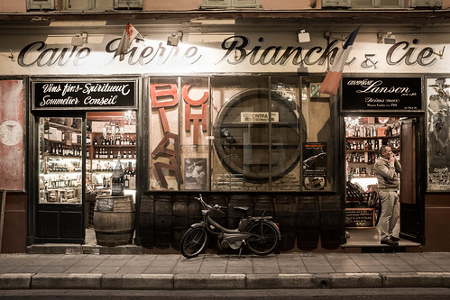 store boutique bottles evening late waiting france nice mobilette vintage smoking man flag signs pavement old wine champagne bike phoning color frontview 2wheels letters lights street sidewalk 1person candidphotography fulllength alpesmaritimes brown europe winery