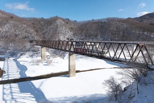 積雪期の五十里湖を渡る列車を湯西川温泉駅前で撮影