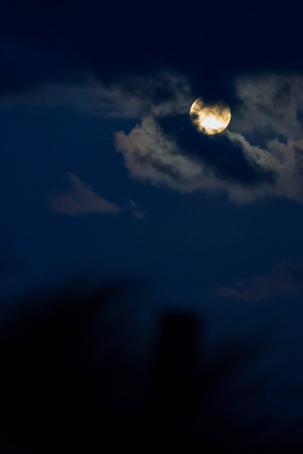 Full moon behind a thin layer of clouds