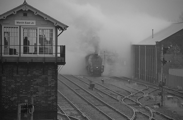 The Box Bobby looks on as 60009 'Union of South Africa' emerges from the Goods Loop and a cloud of steam after a water stop. The Christmas White Rose Tour, Cambridge to York. 20 12 2017 bw