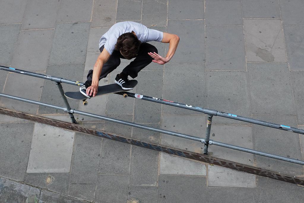 A skateboarder jumps over a rail