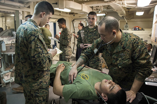 Hospital corpsman examine a patient during a mass causality drill. | by Official U.S. Navy Imagery