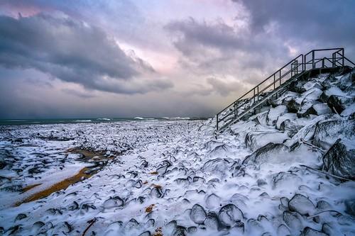 winter iceland snow rocks ocean shore sunset clouds sky rocky stairs perspective landscape northatlantic reykjanespeninsula gardur
