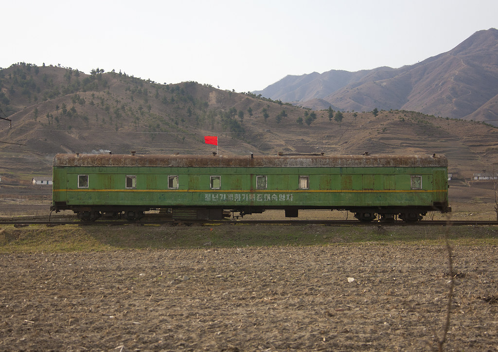 North Korean rusty train with a red flag stopped in the co