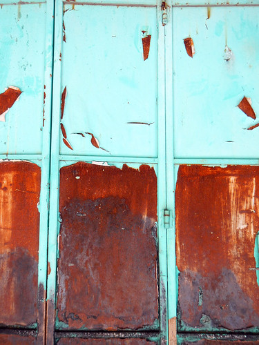 Rusty wall with peeling turquoise paint in Penang, Malaysia