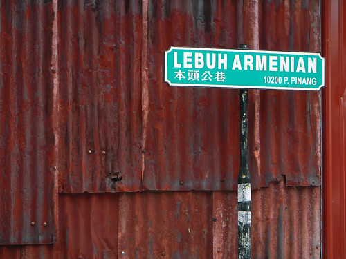 Aqua green street sign in front of a rusty corrugated metal wall in Penang, Malaysia