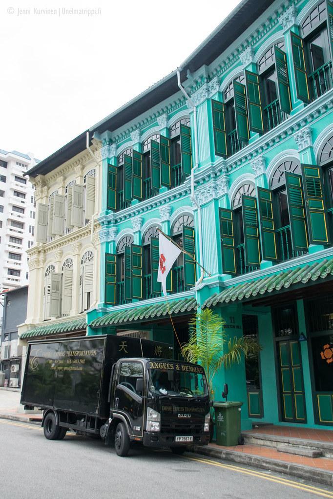 Kuorma-auto Singaporen upeiden vanhojen talojen edustalla