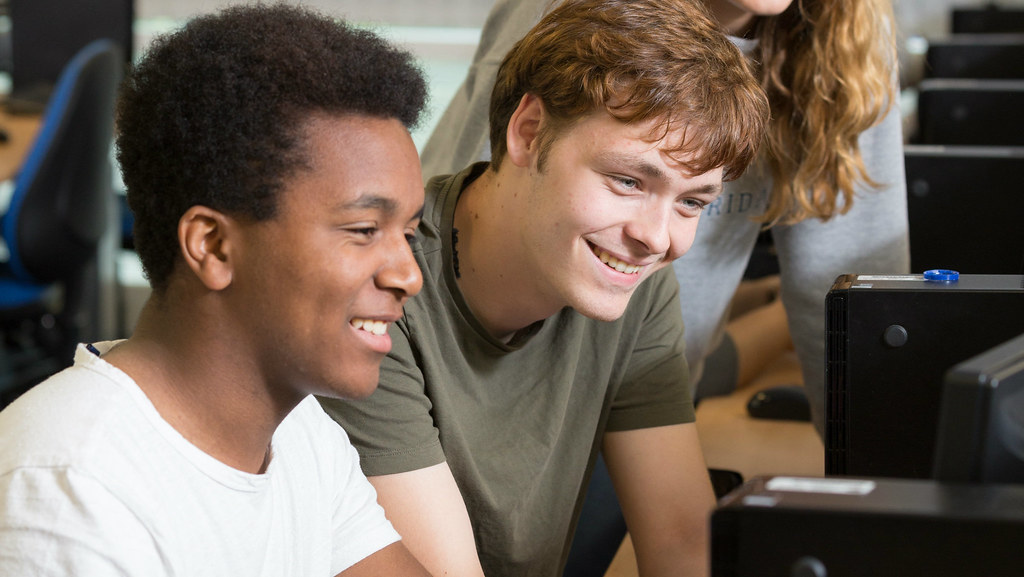 Two male students sat at a computer with their fellow students in the background
