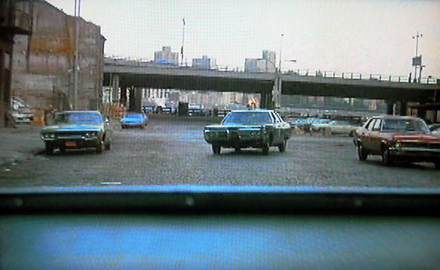 By popular demand... another still from the 1973 season of Kojak.  This shot was taken from the back seat of a criminal's car looking to an NYPD police car giving chase. Cobblestone streets, FDR Drive, East River and Brooklyn in the background. New York