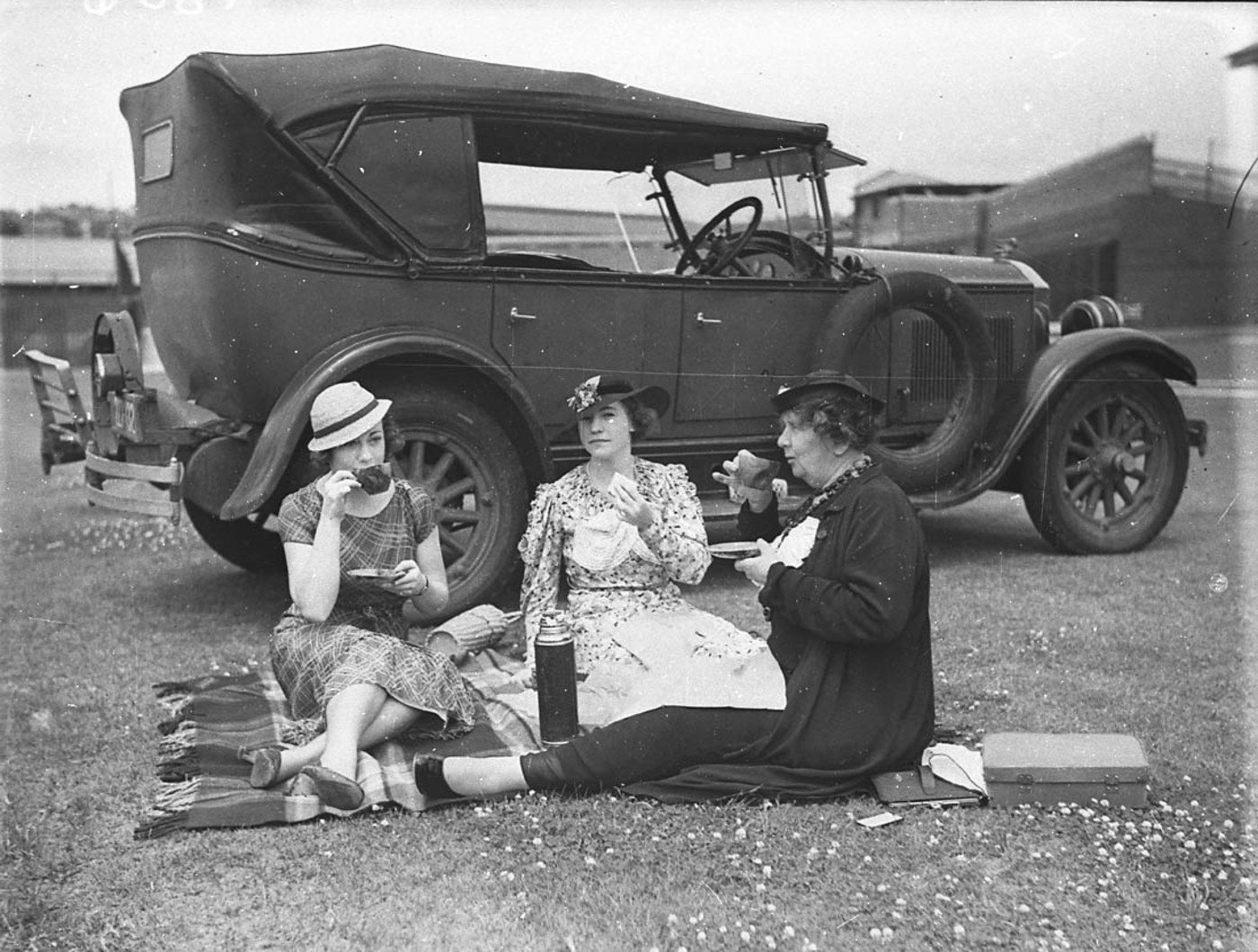 Three women cricket spectators picnicking beside a 1928 Buick during a 2nd XI cricket match between NSW and Victoria at the Sydney Cricket Ground, 27 December 1934, by Sam Hood.