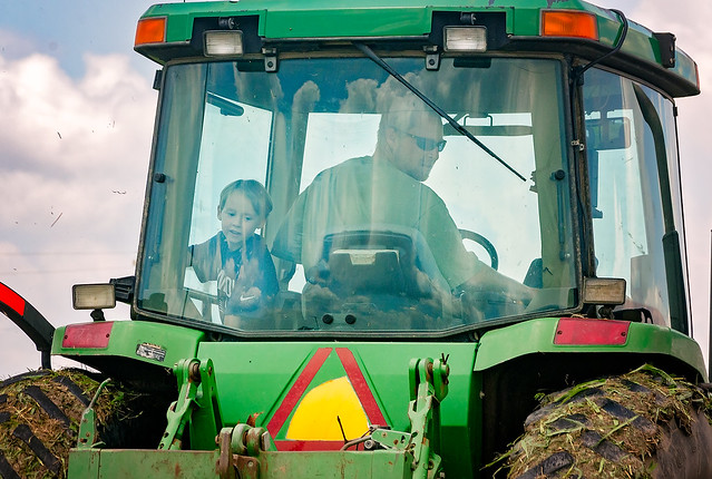 Farmer and son cutting grass in Rosedale Mississippi in the Mississippi Delta