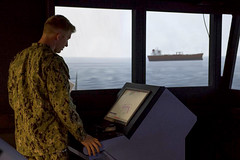 Ensign Zachary David Hirsch, an officer of the deck, checks a monitor from the bridge in a navigation, seamanship and ship-handling trainer during a simulated evolution to evaluate OOD proficiency. (U.S. Navy/MC2 Lenny LaCrosse)