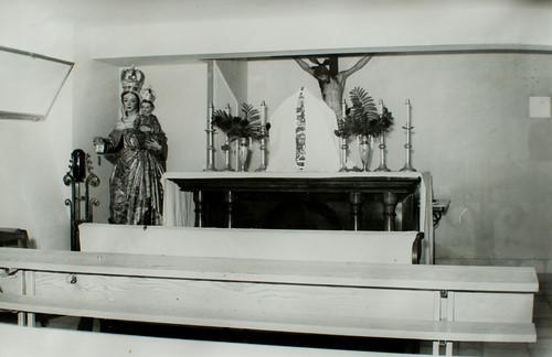 Entrada [2] - Se entra por aquí, por esa verja provisional, prestada. Se empuja la puerta, y, al fondo, el altar.