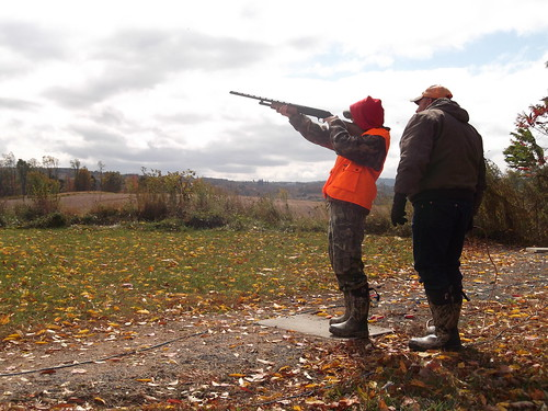 Photo of personal instructor guiding student aiming a shotgun