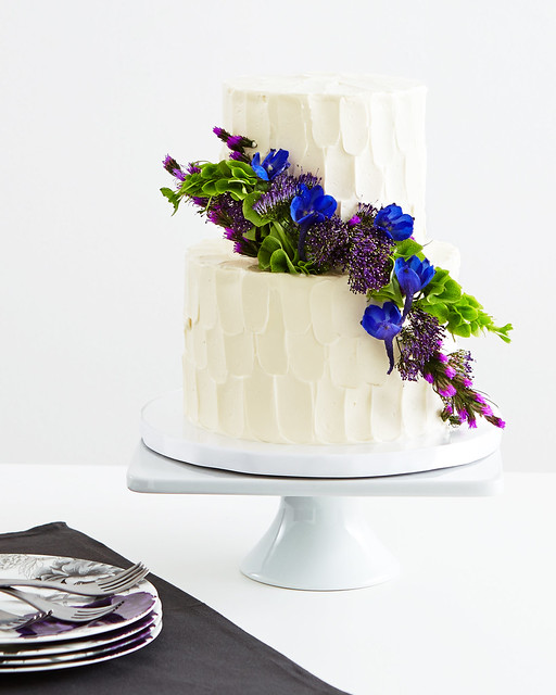 frosted white cakes with delphinium bells of ireland liatris and purple trachelium on white platter stand with plates and silverware