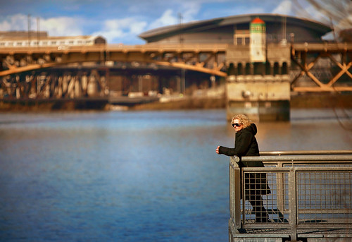 ian sane images solitudewithaview sunlight winter woman long black coat vera katz eastbank esplanade northeast portland oregon candid street photography burnside bridge moda center canon eos 5d mark ii camera ef70200mm f28l is usm lens