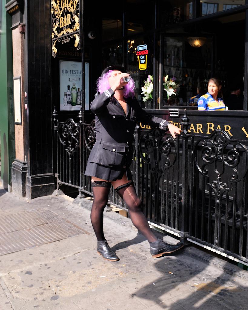 A man in fancy-dress drinks alcohol outside a pub