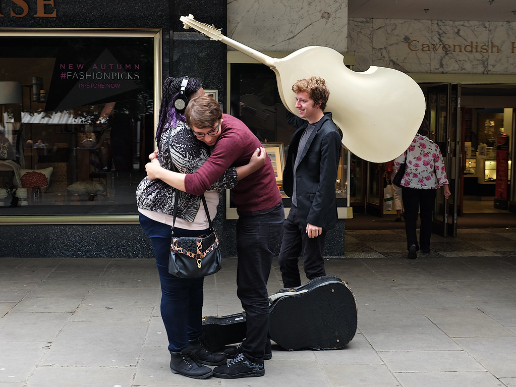 2 people hug as a man carries a double bass on his shoulder