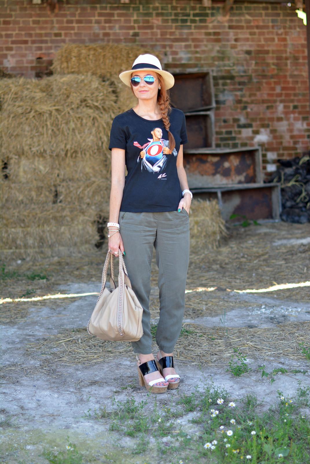 Black graphic tee with Panama hat, khaki track pants, strappy platforms