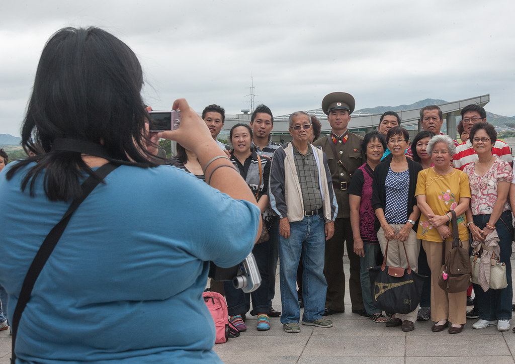 Tourists taking photos with a North Korean soldier on the Demilitarized Zone, North Hwanghae Province, Panmunjom, North Korea