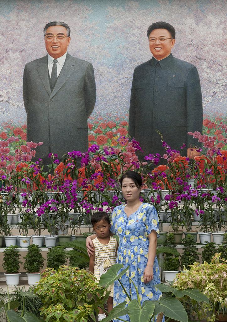 North Korean woman posing in front of the Dear Leaders fresco at the international Kimilsungia and Kimjongilia festival, Pyongan Province, Pyongyang, North Korea