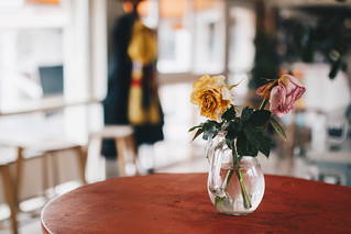 Vase with flowers in a cafe. Colorful blurry background. | by wuestenigel