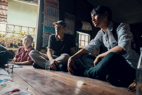 Asian and Western men sitting on floor with food