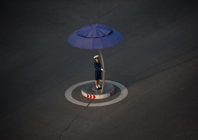North Korean traffic security officer in blue uniform in the street, Pyongan Province, Pyongyang, North Korea