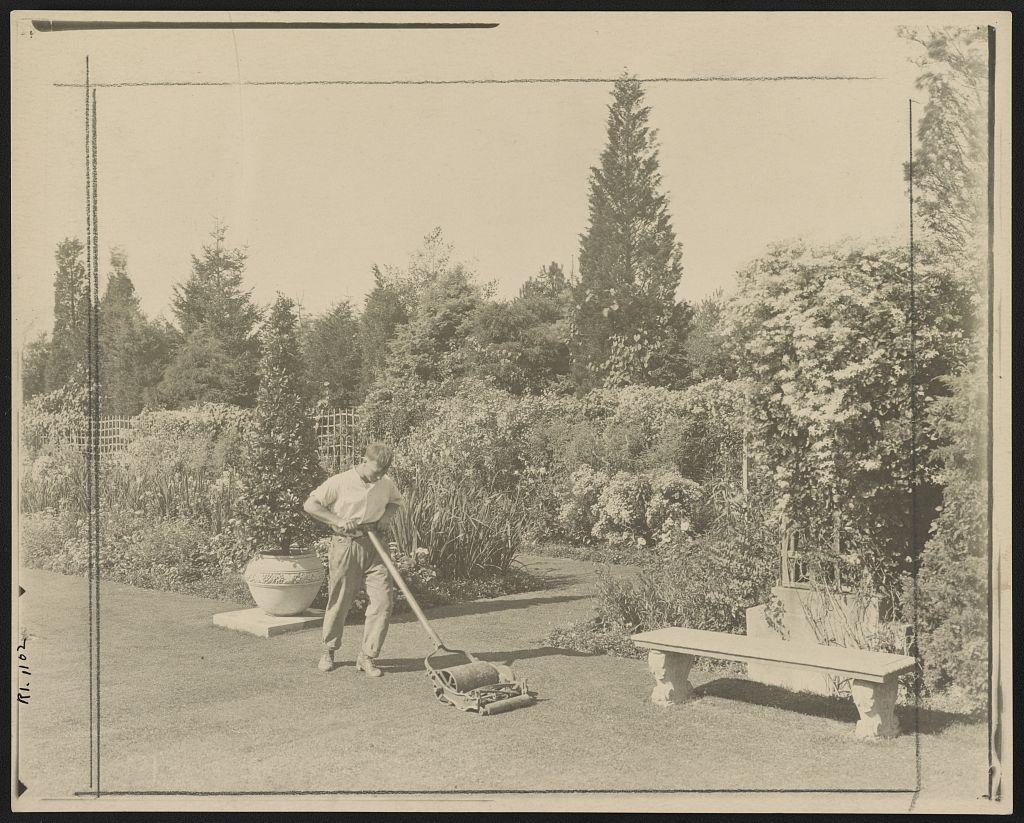 [Gardener pushing lawn mower, posed to illustrate Rudyard Kipling's poem The Glory of the Garden] (LOC)