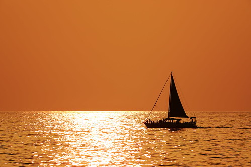water ocean sunset sea boat watercraft sailboat ship sun vessel dawn sky beach evening dusk transportation calm outdoor horizon yacht transport sunrise dinghy large nature morning body outdoors wave backlit sitting dhow floating sunlight top seascape sail orange silhouetted lake wind man seashore afterglow galwayhooker