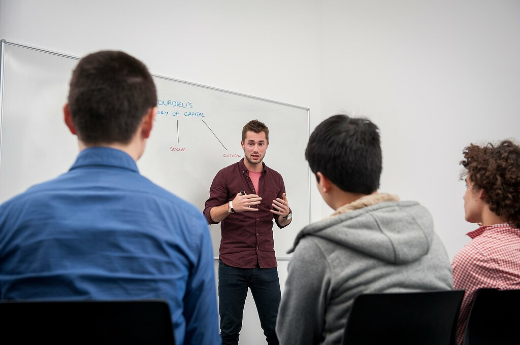 A student presenting to a group of classmates.