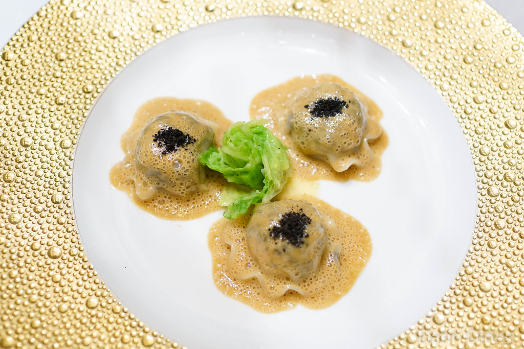 Truffled langoustine ravioli in a foie gras sauce with simmered green cabbage