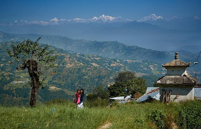 Newari girl carrying baby in front of Himalaya Range, Dulikhel, Katmandu Valley, Nepal