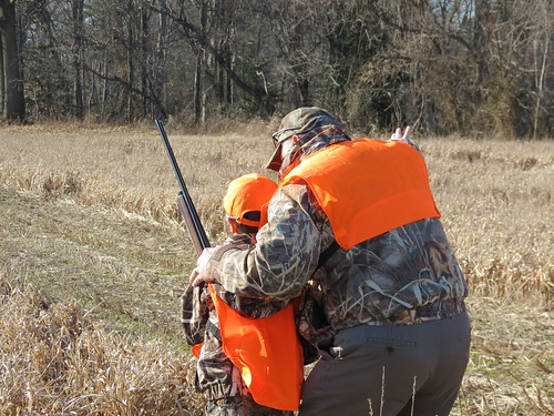 Photo of adult teaching young hunter in a field