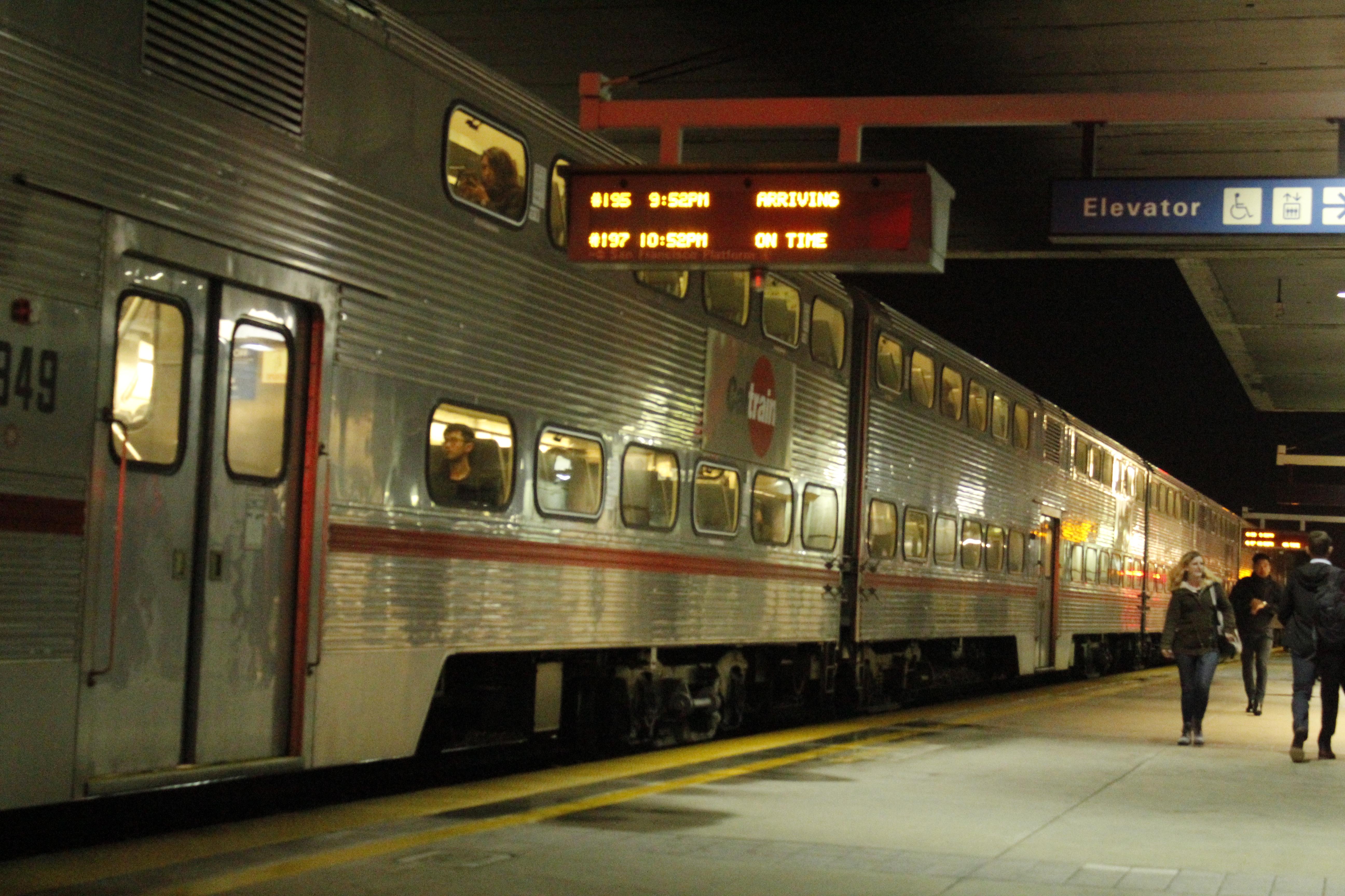A set of Nippon Sharyo passenger cars leaving Millbrae Station for San Francisco