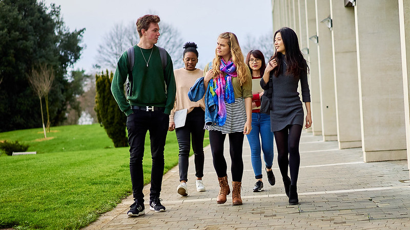 A groups of students, male and female, walking along campus