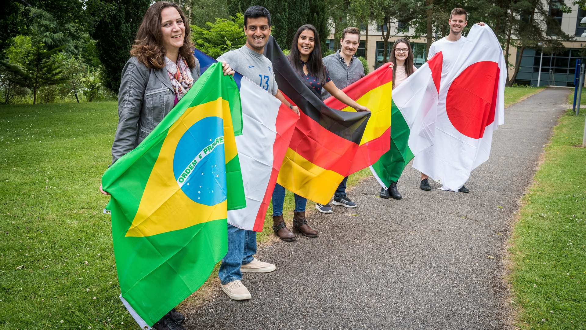 Photo of six foreign language students holding flags of different countries.