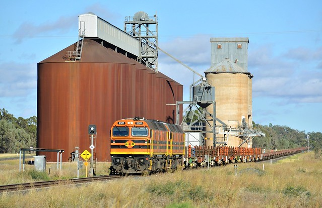 Early on a summer's morning, Locomotives 2207+2212 cruise past the silos at Gunningbland with a loaded railset and an empty rake of container wagons on transfer from South Australia.