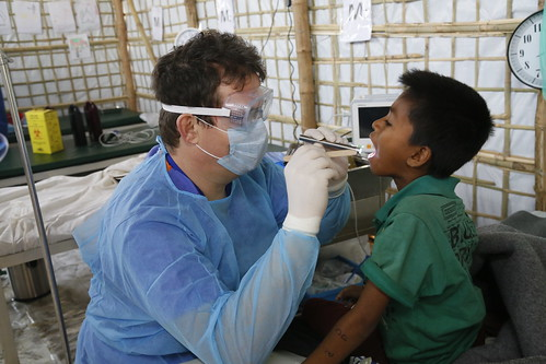 Eight-year-old Saddam, pictured being examined by Dr Iain Lennon of the UK's Emergency Medical Team, in a clinic in the Kutupalong camp for Rohingya refugees in southern Bangladesh, a day after receiving treatment for diphtheria | by DFID - UK Department for International Development