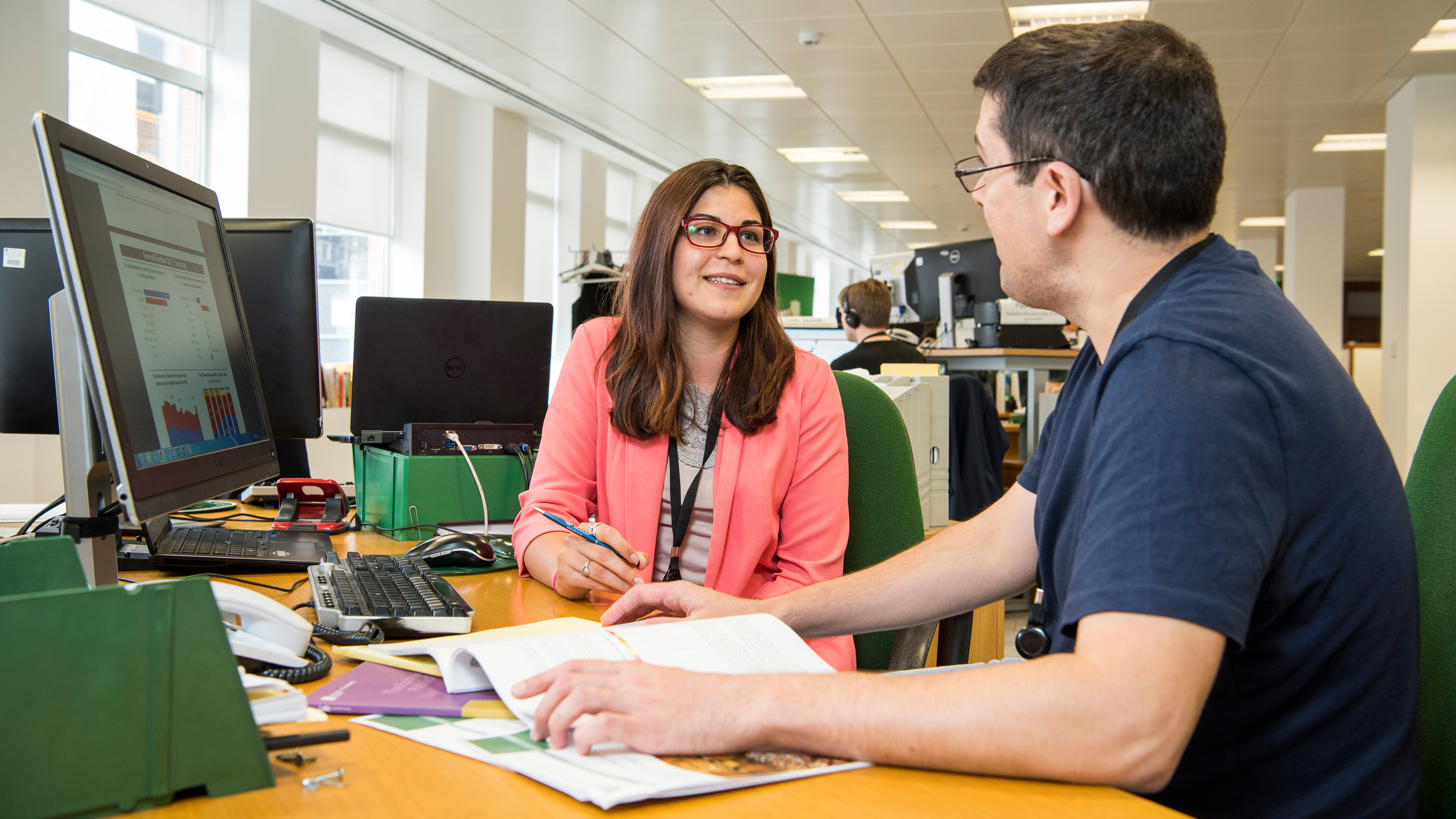Man and a woman at a desk using the system and talking about placements