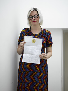 Craftivist Laura Butterworth with her handwritten letter to go with her stitched hanky for Rita Ora, Musician & M&S 'leading lady' in SS14 advertisements | by craftivist collective