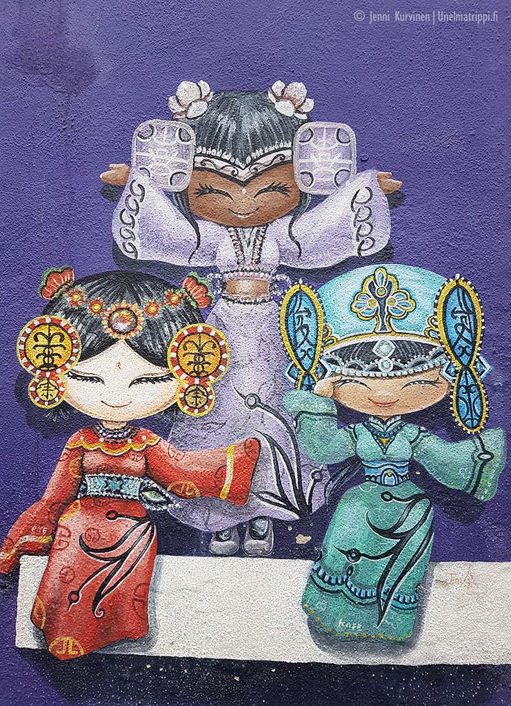 Katutaideteos kolmesta naisesta violetilla taustalla