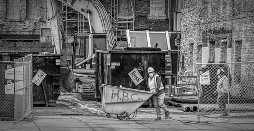 2018 march kevinpovenz grandrapids kentcounty kent downtown afternoon work workers construction constructionworkerswheelbarrowblack whitebwcanon 7d mark iisigma 24105 art outside outdoors sidewalk push dump dumpsters walking pushing street photography streetphotography