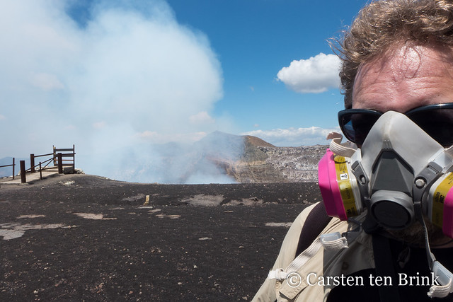 Self-portrait with gas mask and emitting volcano