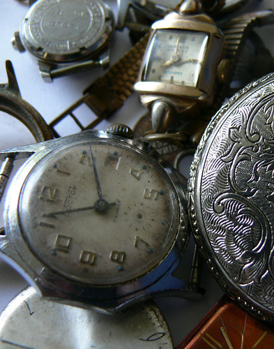 Old timepieces in a pile to prepare for watch repair