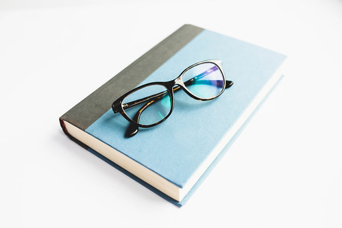 Book with reading glasses on white background | by wuestenigel