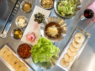 Overview of Apple Samgyupsal's banchan, vegetables and apple slices | by huislaw