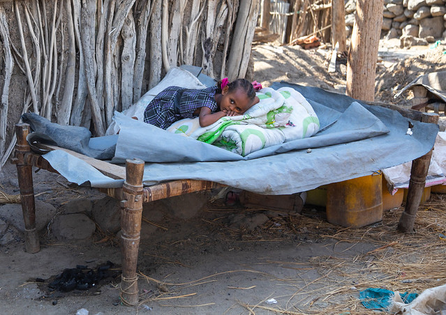 Ethiopian girl resting on a bed in front of her house, Afar Region, Assayta, Ethiopia