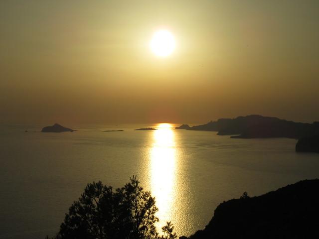 Die Sonne steht tief über dem Mittelmeer. Sie relektiert sich im Wasser und färbt Himmel und Wasser golden ein. Die Felsen und Inseln der Calanques heben sich dunkel dagegen ab.